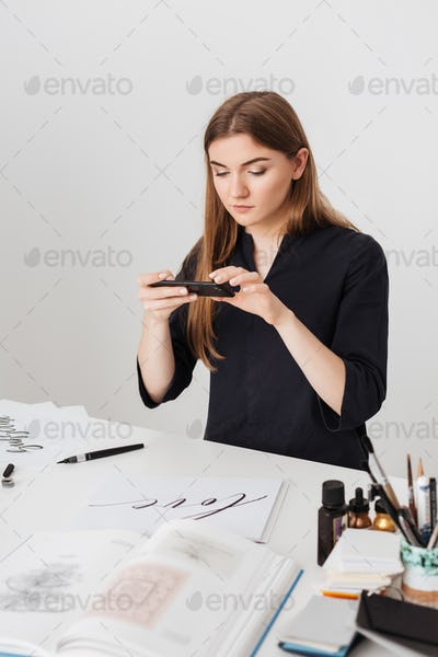 Young beautiful lady sitting at the white desk and taking photos of cool notes on her cellphone