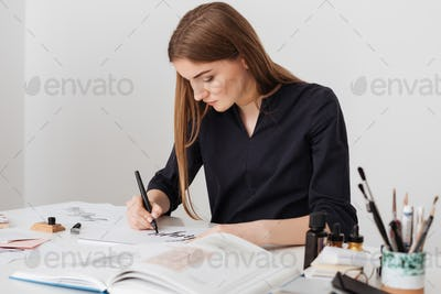 Portrait of young nice lady sitting at the white desk with open book while writing notes on paper
