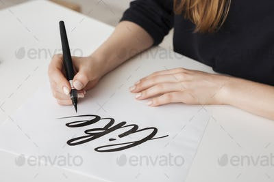 Close up photo of young woman hands writing on paper on desk  isolated