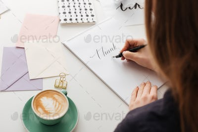 Beautiful photo of woman from backside sitting at white desk and writing notes isolated