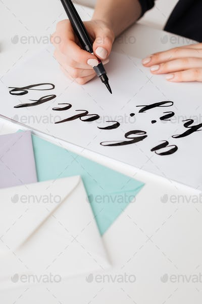 Close up photo of young woman hands writing alphabet on paper on desk  isolated