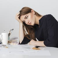 Portrait of young nice lady sitting at the white desk and leaning head on her hand