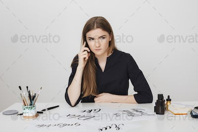 Lady sitting at the white desk and talking on her cellphone while seriously looking aside