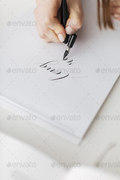 Close up photo of woman hands holding pen and writing  beautiful postcard isolated