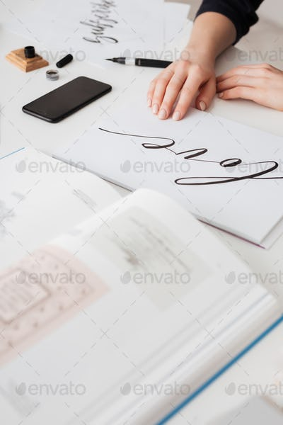 Photo of young woman hands with beautiful notes and open book on desk isolated