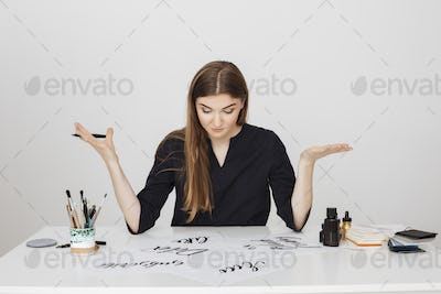 Young pretty lady sitting at the white desk with pen in hand and thoughtfully looking at papers