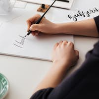 Beautiful photo of woman hands holding classic ink pen while writing notes on white desk