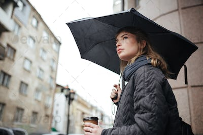 Pretty lady standing on street with black umbrella and coffee in hands while dreamily looking aside