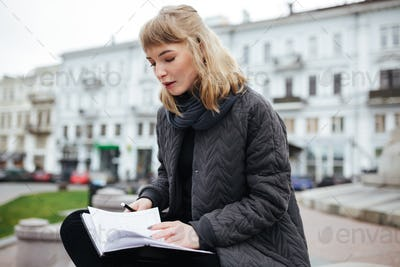 Beautiful girl with blond hair sitting with notebook in hand on city street
