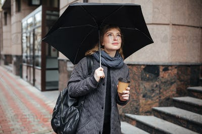 Young cute lady standing on street with black umbrella and coffee in hands