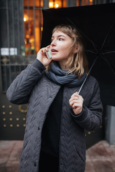 Portrait of young nice lady standing on street with black umbrella and talking on her cellphone