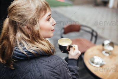 Close up photo of pretty lady sitting at the table on street and drinking coffee isolated