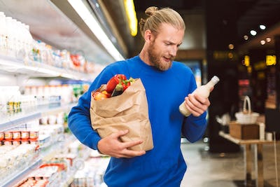 Young man in dark blue sweater holding paper grocery bag full of