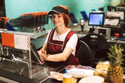 Pretty smiling female cashier in uniform happily using cashbox w