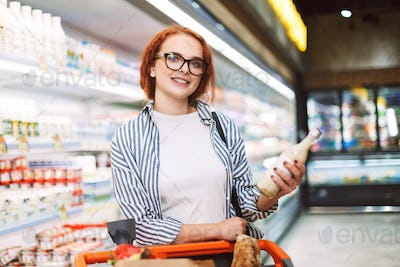 Smiling girl in eyeglasses and striped shirt with shopping cart