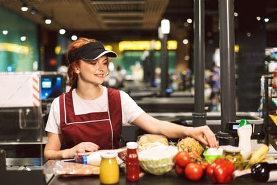 Young female cashier in uniform happily looking aside with produ