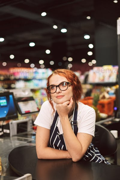 Young pretty cashier in eyeglasses and striped apron leaning on