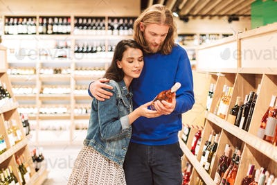 Young beautiful couple dreamily choosing wine together in superm