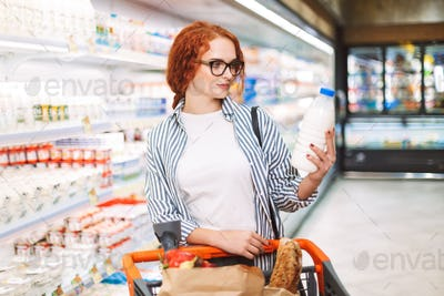 Pretty girl in eyeglasses and striped shirt with trolley full of
