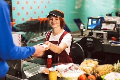 Pretty smiling female cashier in uniform happily working in supe