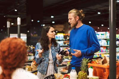 Young couple near cashier desk emotionally discussing something