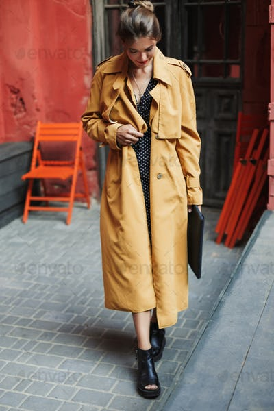 Young beautiful smiling woman in trench coat and boots holding b