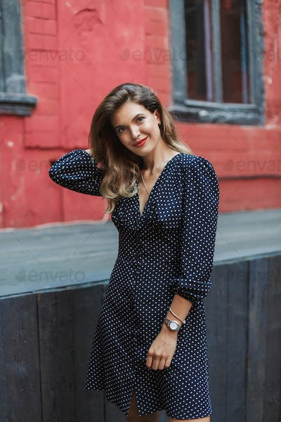 Young attractive woman in black polka dot dress with red lips ha