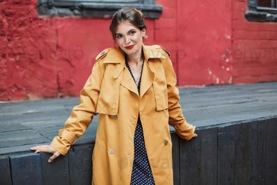 Young beautiful smiling woman in orange trench coat and black po