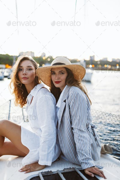 Young beautiful woman in white shirt and pretty lady in stripped