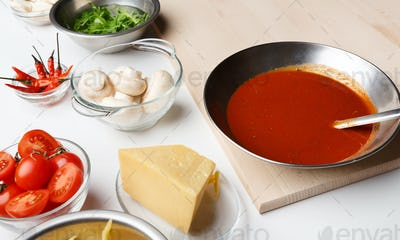 Pizza cooking ingredients. Cheese, mushrooms and sauce in bowls