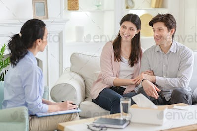 Counselor and happy couple after effective marital therapy