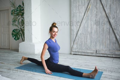 Woman workout at home. Doing splits and turned on blue mat.