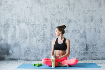 Fitness woman relaxing after class in gym.