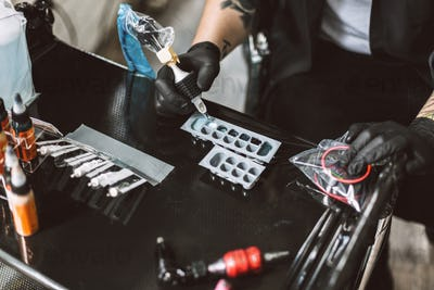 Close up tattoo master in black gloves preparing tattoo machine