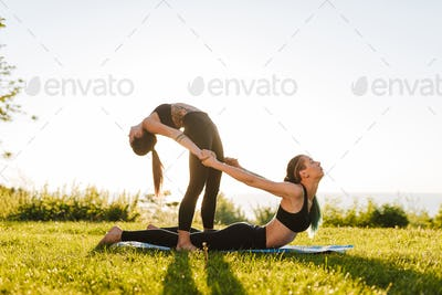 Photo of two beautiful ladies in black sporty tops and leggings training yoga poses together