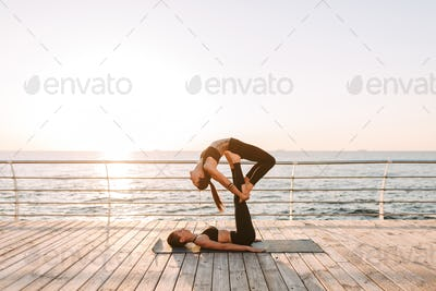Photo of two beautiful ladies in black sporty tops and leggings training yoga poses by the sea