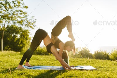 Young ladies in black sporty tops and leggings training yoga poses together