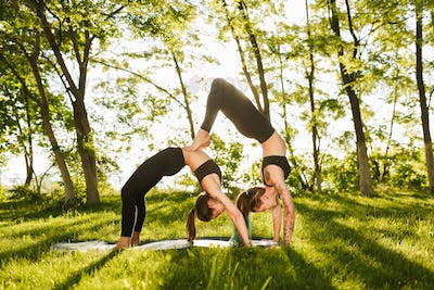 Photo of two pretty ladies standing in bridge poses while training yoga together outdoors
