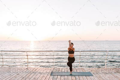 Photo of pretty lady standing and training yoga poses by the sea