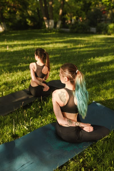Young ladies in black sporty tops and leggings sitting from back and training yoga poses together