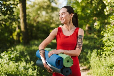 Smiling lady in red jumpsuit standing with yoga mats in hands and joyfully looking aside in park
