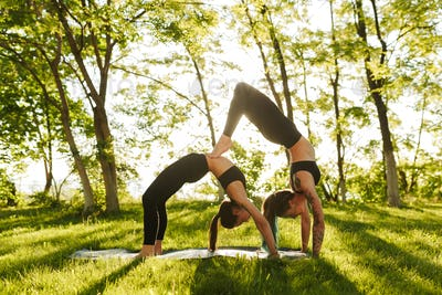 Two young ladies in black sporty tops and leggings training yoga poses together
