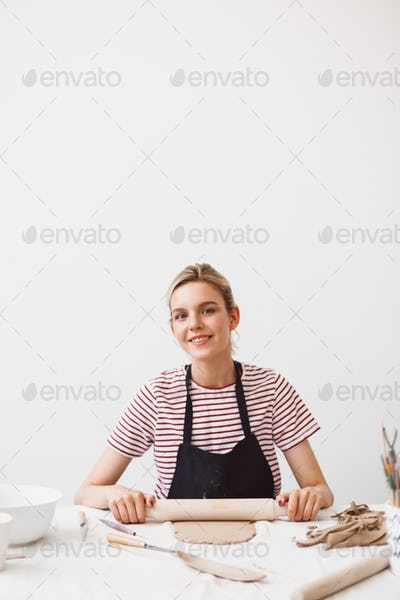Girl in black apron and striped T-shirt sitting at the table with rolling pin and working with clay