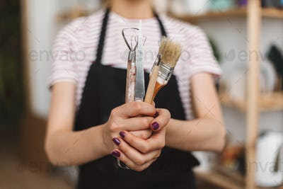 Close up of girl holding pottery tools in hands over black apron at pottery studio