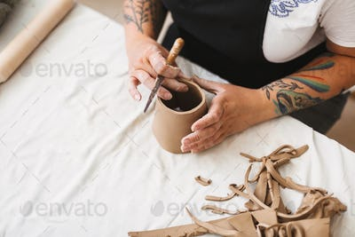 Close up woman hands with colorful tattoo working with clay and creating ceramic object