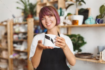 Smiling girl in black apron and white T-shirt holding handmade mug in hands