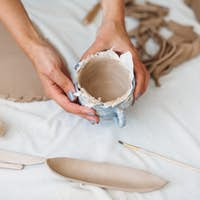 Close up woman hands working with clay and molding bowl at pottery studio