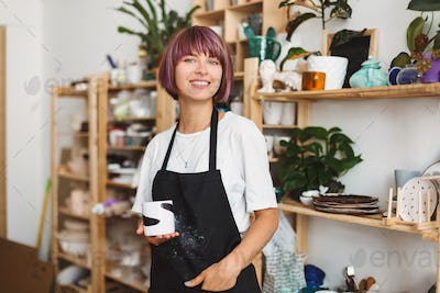 Beautiful girl with colorful hair in black apron and white T-shirt holding handmade mug in