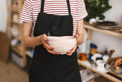 Close up of girl holding handmade bowls in hands over black apron at pottery studio