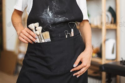 Close up girl standing with brushes and pottery tools in pocket of black apron at pottery studio